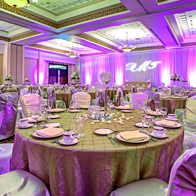 Image of Grand Ballroom C and D set for a wedding with white drape, a monogram GOBO, gold table cloths, white chair covers with gold sashes, floral and candle centerpieces, and uplighting.