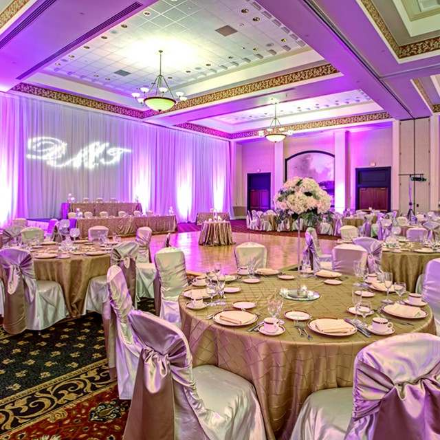 Image of Grand Ballroom C and D set for a wedding with a dance floor, head table, tables with linens and chairs with chair covers.