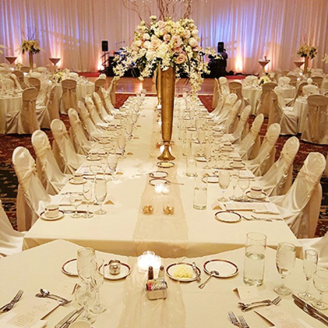 Image of the head table for a wedding in the Grand Ballroom with a beautiful flower centerpiece, dance floor, white drape, uplighting and fairly lights hanging from the ceiling.