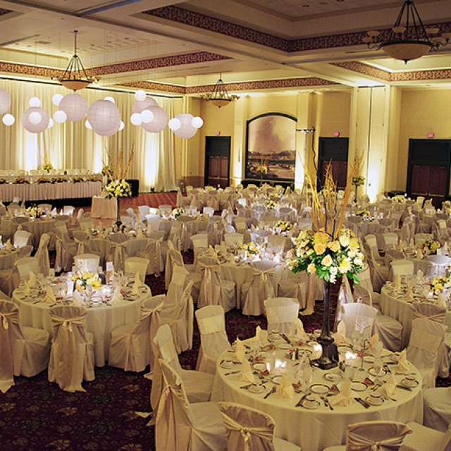 Image of the Grand Ballroom set for a wedding with white lanterns hanging from the ceiling, above the dance floor, the head table up on a stage, white table cloths and chair covers, and yellow floral centerpieces.