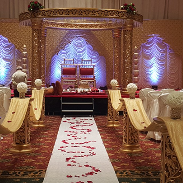 Image of a wedding mandap setting in the Grand Ballroom with chairs set theater style with white chair covers and a stage with two red chairs and drape behind them with uplighting.