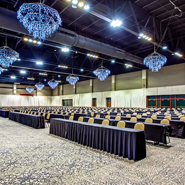 Image of North and South Exhibit Hall carpeted, with drape in classroom seating with a stage and projection screens.