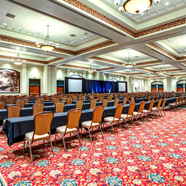 Image of entire Grand Ballroom set in classroom seating with a stage, podium and two projection screens.