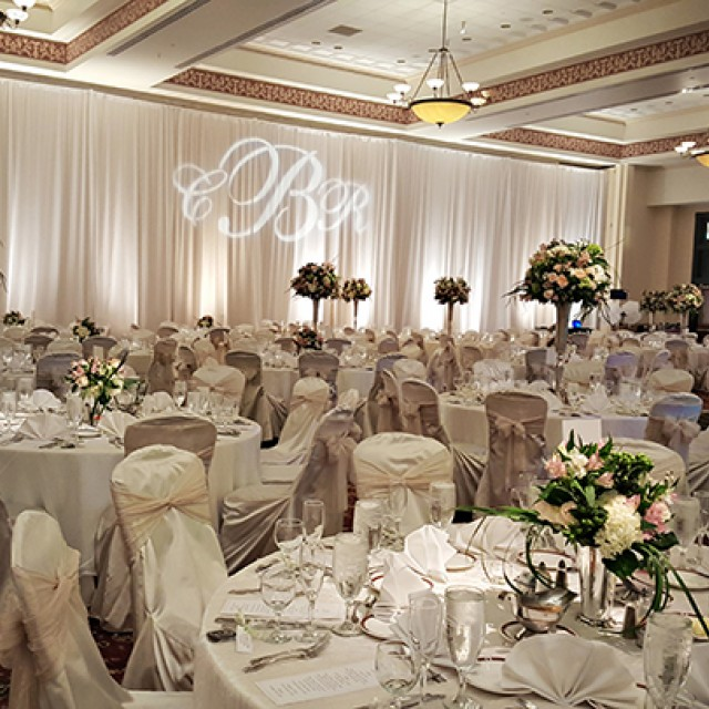 Alternate Text: Image of the Grand Ballroom set for a wedding with banquet tables, white drape, a monogram GOBO, floral centerpieces, white chair covers and sashes.