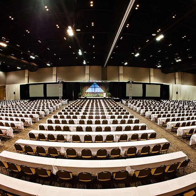 Image of classroom seating in the North and South Exhibit Hall with a stage, drape and four projection screens.
