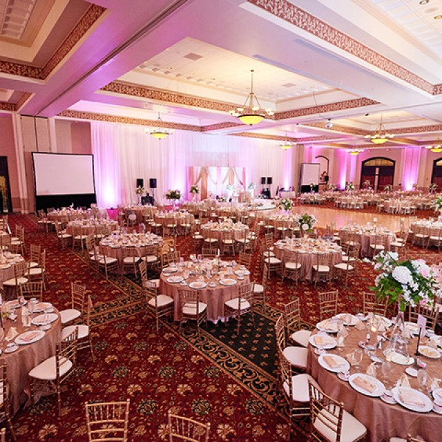 Image of Grand Ballroom set for a wedding with banquet tables, a dance floor, stage, projection screen and pink uplighting.
