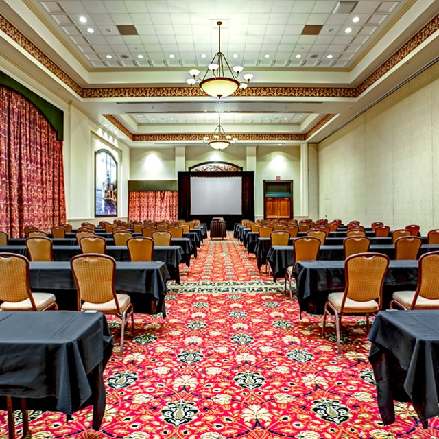 Image of Grand Ballroom A set in classroom seating with one projection screen at the front of the room.