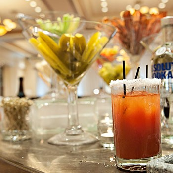 Image of a Bloody Mary Bar with premade Bloody Mary and bacon, pickles and other accompaniments in the background.