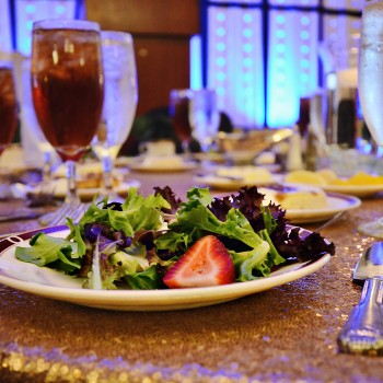 Image of a salad and table place settings on a sequin table cloth.