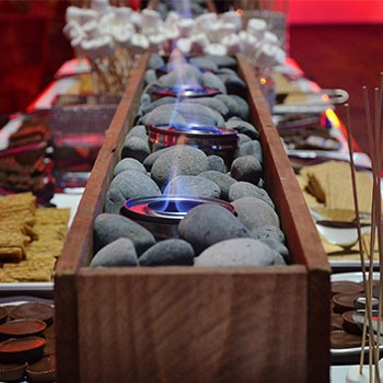Image of a S'mores Bar action station with wood containers filled with river rocks and sternos for roasting marshmallows and marshmallows, chocolates, and graham crackers lined up on either side of the containers.