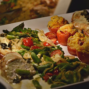 Image of a platter with two rows of vegetables and two rows of chicken.